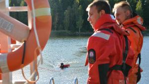 En person i röd overall är i vattnet. Han håller i en flytlbräda och någon drar honom mot land. På bryggan står två män i orange overaller.