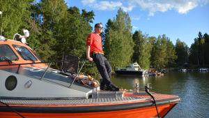 En man i röd t-tröja står lutad i fören på en båt.