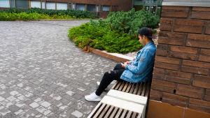 Poika istuu yksin penkillä ulkona ja nojaa koulun seinään
