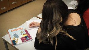 Takaa kuvattu tyttö tekee suomenkielen tehtäviä luokassa