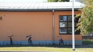 En bild på ett hus. Framför huset står tre cyklar i en cykelställning och brevid huset växer rönnbär.