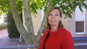 En blond kvinna i röd kavaj står på gatan under ett träd med tre stammar och blickar uppåt.
