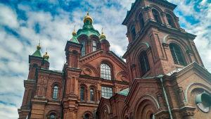 Uspenskijkatedralen på en solig men lite molnig sommardag. I bilden tornar katedralen upp framför fotografen.