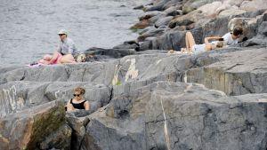 Solbadare på klipporna vid Eirastranden i Helsingfors.