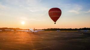 En ballong landar på Malms flygplats. I bakgrunden solnedgång.