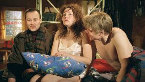 Sängyllä istuu kaksi miestä ja yksi nainen. Toinen miehistä on pukeissa, nainen ja toinen mies on vähissä vaatteissa. Nainen näyttää hämmentyneeltä.
