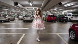 En kvinna klädd i så kallade Lolitakläder - en fluffig vit och rosa klänning med spetsar på. Hon har vita högklackade skor och blommor i håret. Hon står i en parkeringsgrotta.