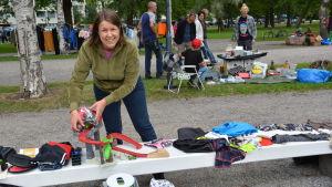 Sanna Isomäki står och säljer saker vid en bänk.
