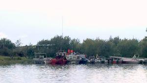 Båtar med såväl civila som frivilliga brandkårister på plats för att släcka stugbrand på Norra Rönnskärsgrund.