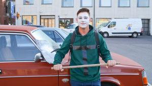 jani framför sin röda bil i teatersmink