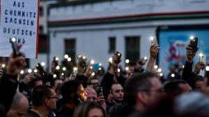 Demonstranter i Chemnitz håller upp upplysta mobiltelefonskärmar i kvällsmörkret.