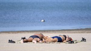 Två personer solbadar på en sandstrand.