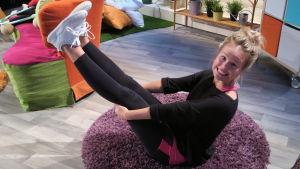 BUU-Klubbens programledare Malin gör en rolig rörelse på golvet i studion.