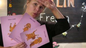 BUU-klubbens programledare Malin fläktar sig med Hoppa På-korten i studion.