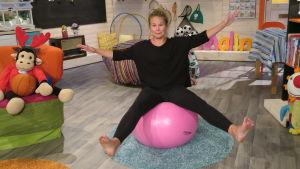 BUU-klubbens programledare Malin balanserar på en jumppaboll i studion.
