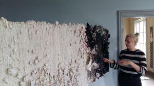 Mirva Kuvaja står vid med sin vävda pappersmatta.