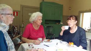 Merja Markkula dricker kaffe med två besökare på Kustö konstgård.