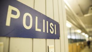 """Helsingin Ratsupoliisin tallin päätyovessa on kyltti, jossa lukee """"Poliisi""""."""