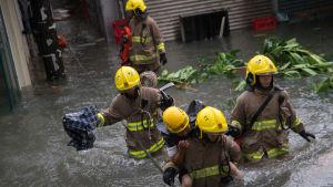 Räddningsarbetare evakuerar invånare i den översvämmade stadsdelen Lei Yu Mun i Hongkong