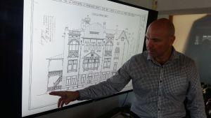 Arkitekt (SAFA) Janne Helin visar på en husritning från början av 1900-talet var ingången till det nya hotell Hamburger Börs kommer att finnas.