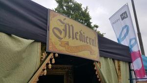 Skylt där det står Medieval vid ett tält med grön ridå och Svenska Yles vimpel i bakgrunden.