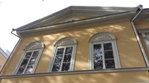 Palmetter bildar ornament ovanför tre fönster på ett gult nyklassicistiskt hus.