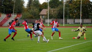 En Musa spelare håller bollen omringad av många BK-spelare.