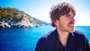 Mies etualalla, hymyilee. Takana näkyy sininen meri ja kallioinen saari.