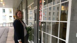 En kvinna står framför en glasdörr.