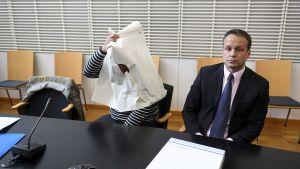 den misstäkta döljer sitt huvud under ett stort papper, med ett litet hål för att kunna se. Bredvid sitter advokaten.