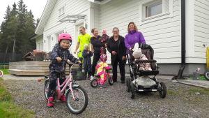 Barnfamiljer samlade framför ett vitt hus i Replot.
