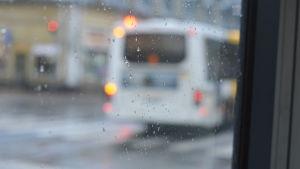 En buss syns suddigt genom ett fönster.