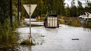 Bil på översvämmad väg