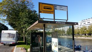 En busshållplats vid Åbo stadsteater, med reklam för Sokos.