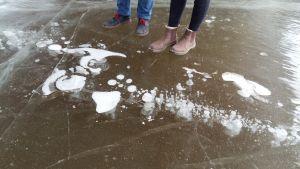Två par skor står vid bubblor som frusit fast i isen.