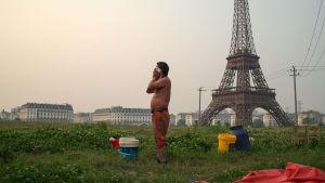 Mies pyyhkii naamaansa rätillä, taustalla näkyy kaupunki ja keskellä vihreää peltoa kopio Eifel Tornista.