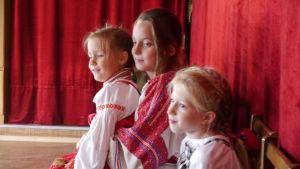 kolme tyttöä istuu salissa, punaisia kansallispukutyyppisiä vaatteita päällään.