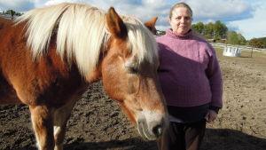 En kvinna (Mervi Piispanen) står bredvid en häst (Pahe).
