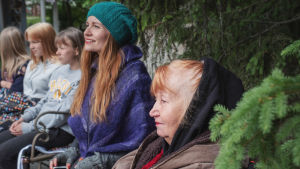 Viisi naista istuu rivissä katsoen keskittyneesti jotakin vasemmalla puolella, kuvan ulkopuolella. Etualalla kuusenoksa.