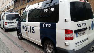 Två polisbilar på en gata i staden.