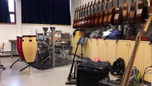 Gitarrer, trummor och musikinstrument i bakre delen av musikklassen.