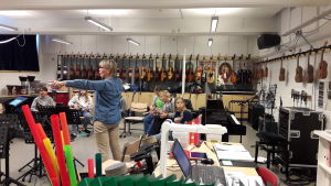 Musiklärare Marina Lindholm står mitt i klassen och instruerar elever som sitter i ring med musikinstrument i famnen.