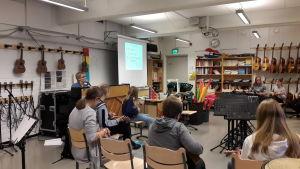 Elever sitter i ring och spelar ukulele medan musiklärare Marina Lindholm ackompanjerar vid pianot.