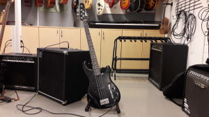 Närbild på svart elgitarr och förstärkare i musikklass.