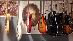 En plansch av Mozart skymtar bakom en rad gitarrer som hänger i taket.