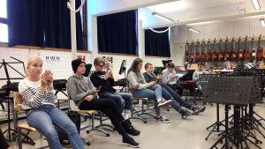 Skolelever sitter med mobiltelefoner i händerna på musiklektionen.
