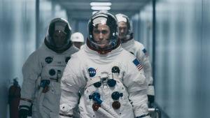 Neil och två andra astronauter går rakt mot kameran i full mundering.