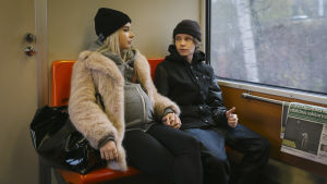 Lenni och Kiira håller varandra i handen i tunnelbanan.