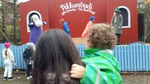 Ett barn i grönturkos regnrock sitter i sin mammas famn och tittar på en teaterföreställning i Muminvärlden i Nådendal.