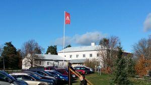 En röd Axxell-flagga vajar utanför den vita huvudbyggnaden vid enheten i Brusaby i Kimito